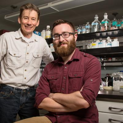 U. of I. professor Ken Paige, standing, and graduate student Miles Mesa study the molecular underpinnings of plant defenses.