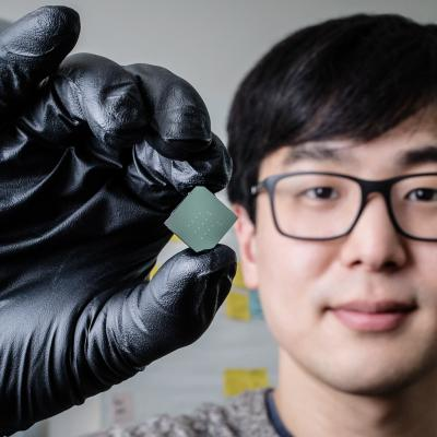 llinois mechanical science and engineering student and lead author of a new study Benjamin Sohn holds a device that uses sound waves to produce optical diodes tiny enough to fit onto a computer chip.