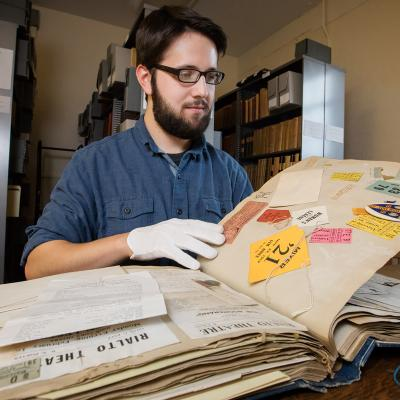 Information sciences graduate student Joseph Porto searches through the scrapbook of a student who attended the university 100 years ago.