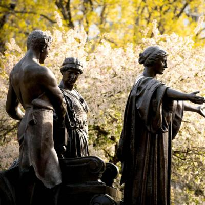 Statue of Alma Mater with Learning, and Labor in front of yellow and white spring blooming trees.